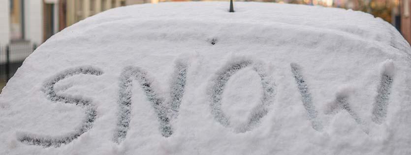 snow écrit sur la vitre arrière d'une voiture enneigée